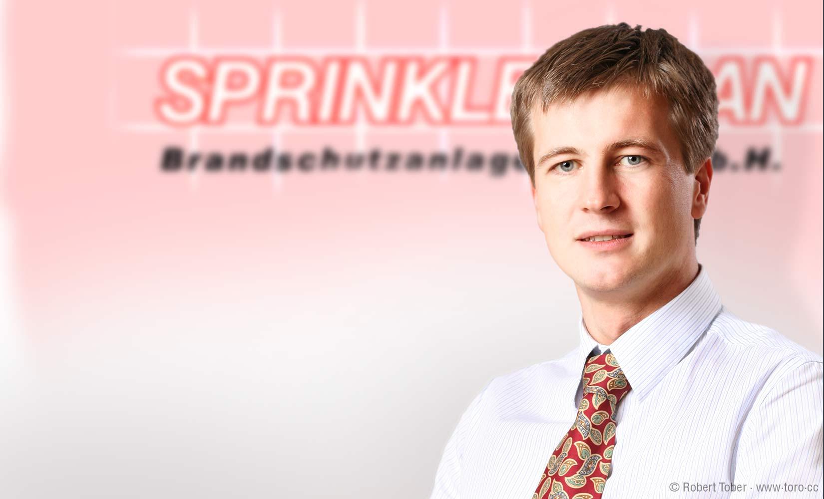 Ing. Werner Hoyer-Weber vor dem alten Sprinklerplan-Logo © Robert Tober