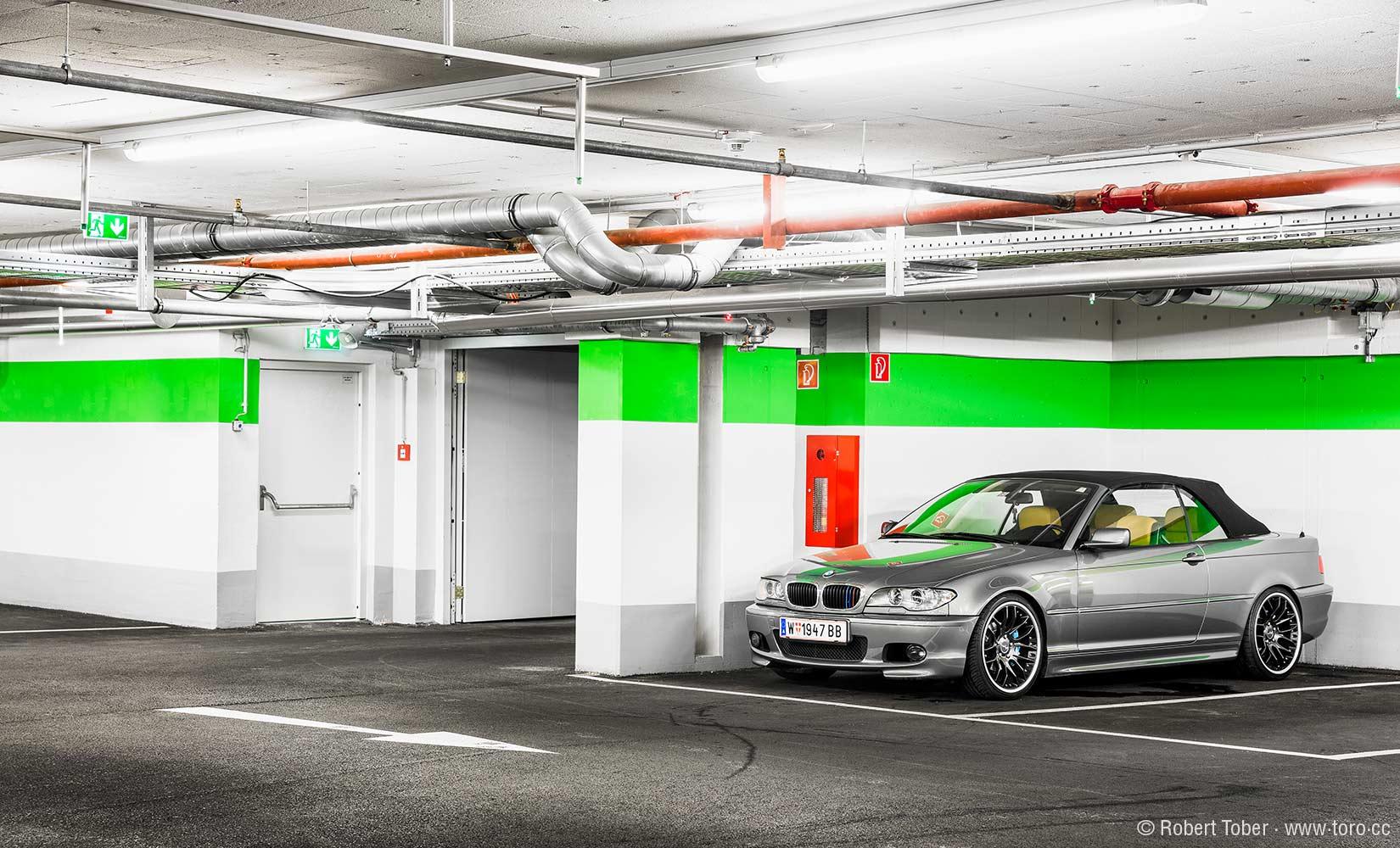 Tiefgarage mit einem BMW M Cabrio. Sprinkleranlage an der Decke, Wandhydrant und Fluchtwegskennzeichnungen © Robert Tober