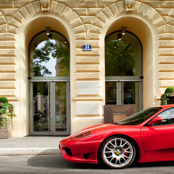 Eingang des Palais Hansen Kempinski mit davor geparktem Ferrari © Robert Tober