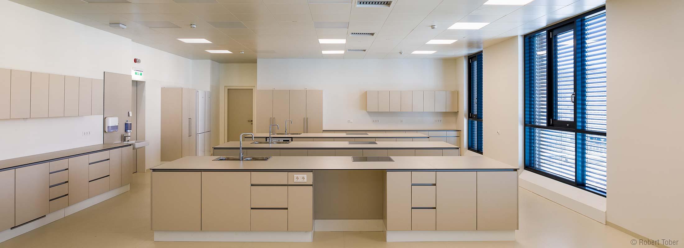 Modern eingerichtete Kochplätze für Hauswirtschaftslehre. Christine Nöstlinger Campus Wien. © Robert Tober