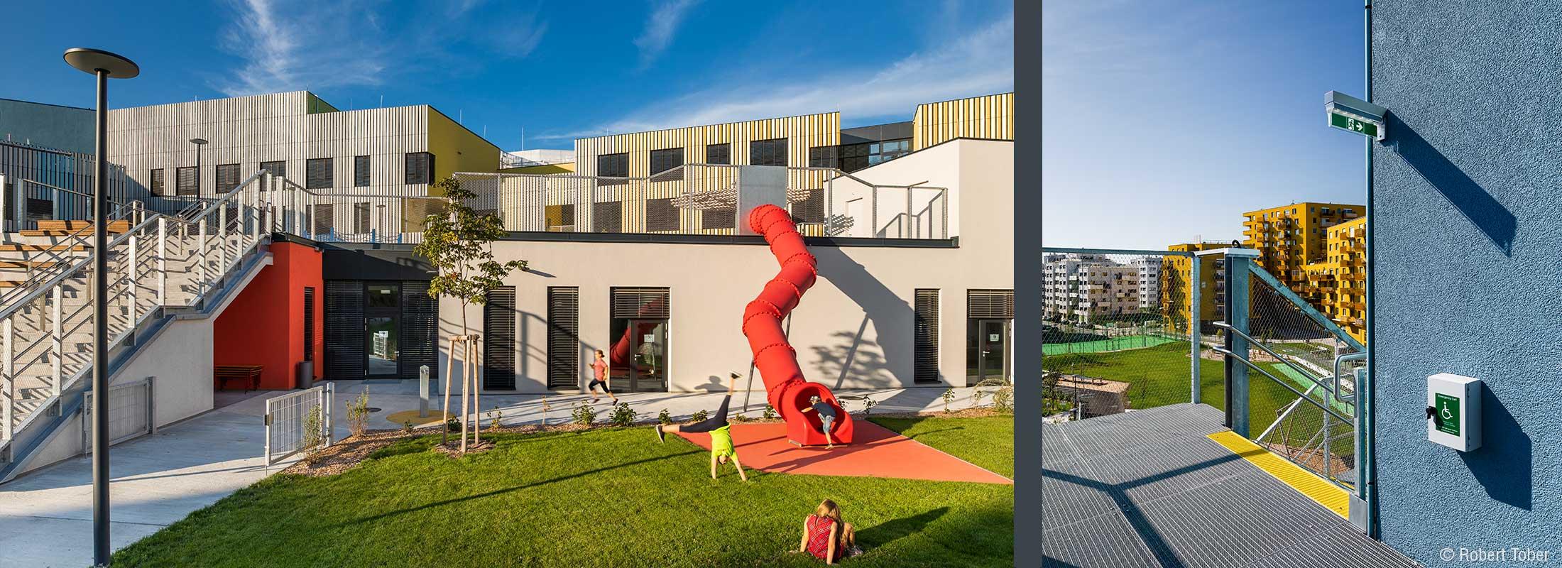 Aussenbereich mit Spielenden Kindern und einer XXL-Rutsche. Fluchtweg über eine Aussentreppe. Christine Nöstlinger Campus Wien. © Robert Tober
