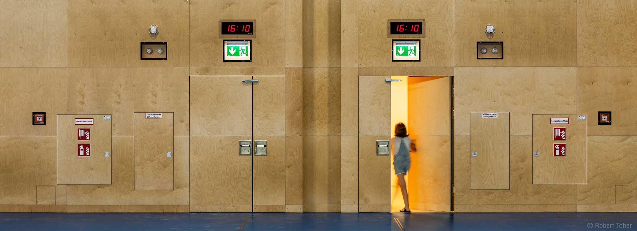 Wandhydrant, Feuerlöscher und Brandschutztüren im Turnsaal. Christine Nöstlinger Campus Wien. © Robert Tober