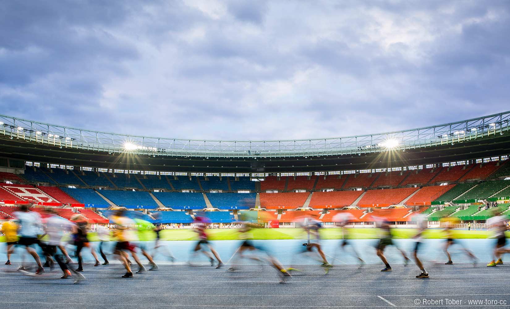 Der Ernst Happel Stadion in der Abenddämmerung. Im Vordergrund Läufer mit Bewegungsunschärfe. © Robert Tober