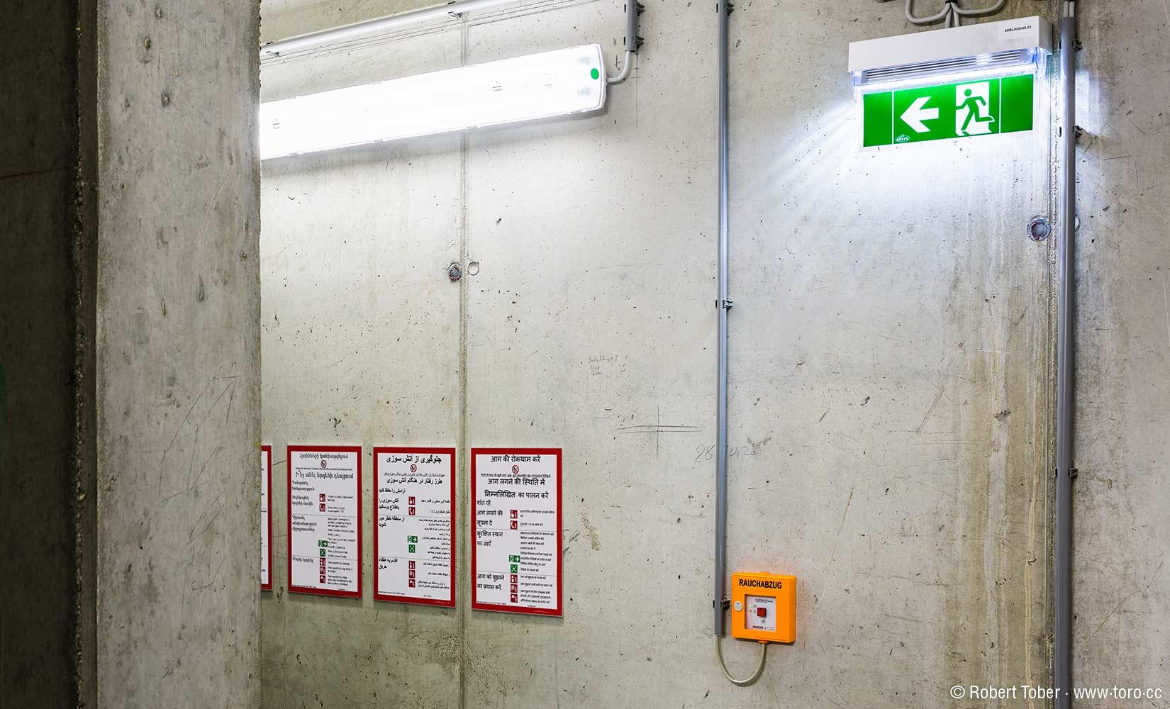 Tafeln mit Brandschutz-Hinweisen in verschiedenen Sprachen, Fluchtwegskennzeichnung, Sichtbeton © Robert Tober
